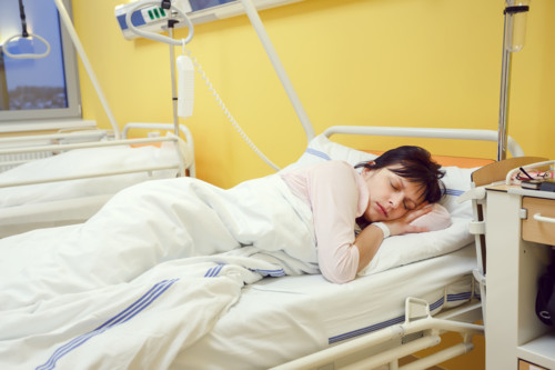 Real people in real situation, sad middle-aged woman lying in hospital with pneumonia